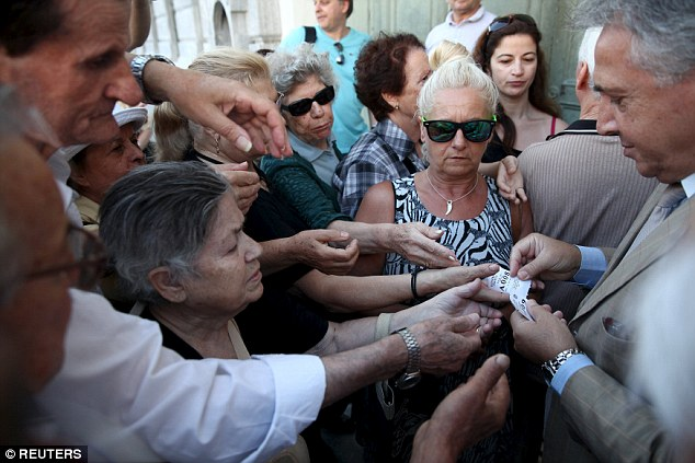 Scuffles: Elderly Greeks were seen pushing and shoving outside banks in the capital Athens this morning as the fought for priority tickets to be allowed to enter banks and withdraw their pensions