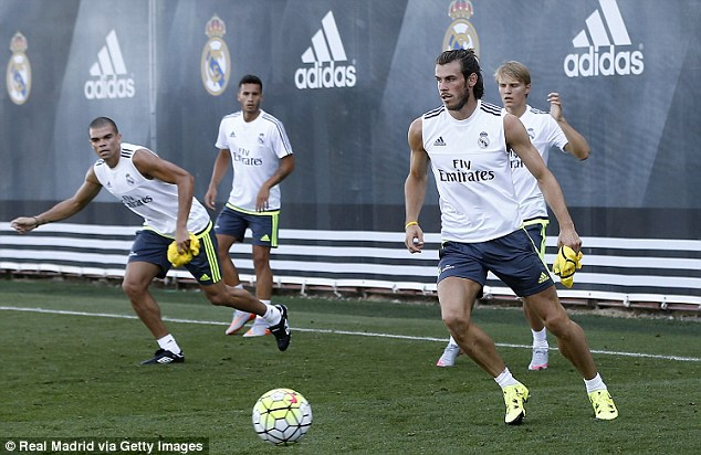 Bale (right) prepares to play a pass during pre-season training with Madrid
