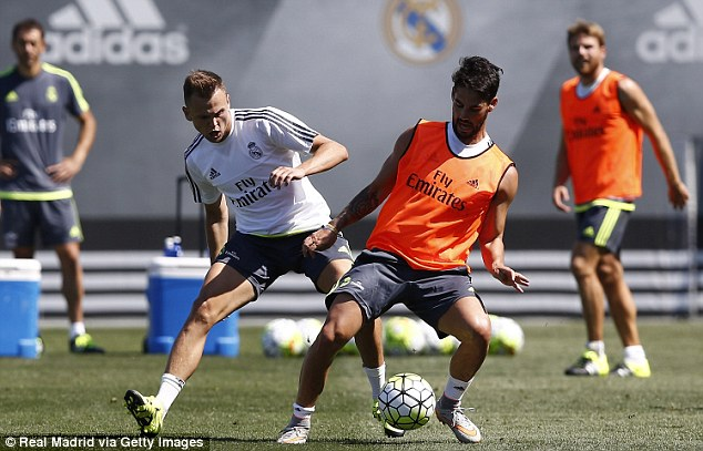 Isco (right) shields the ball as Denis Cheryshev (left) comes in for the tackle during a training session