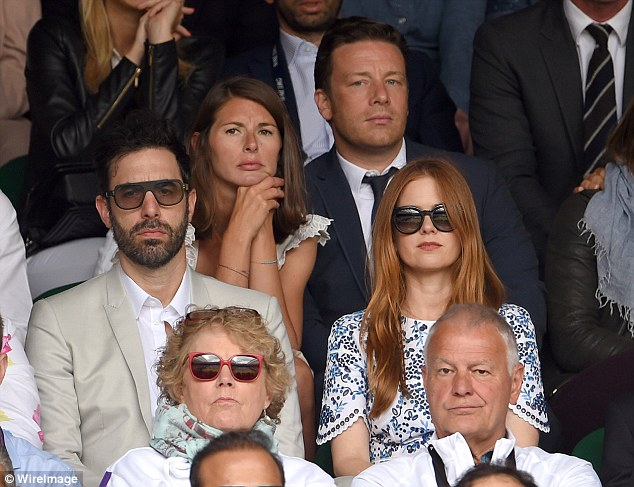 Look who's behind us! Sacha and Isla look super serious as Jamie Oliver and wife look on