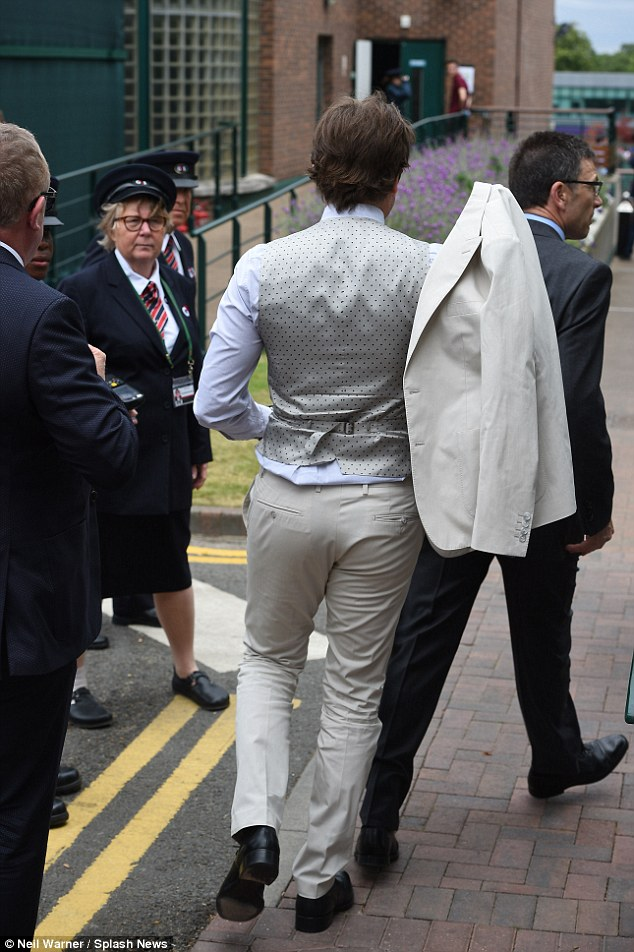 Dotty about tennis? Bradley makes his way into Centre Court, flanked by Wimbledon officials