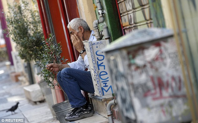 Hopeless: A vendor sits on the steps in front of his shop in central Athens earlier this morning