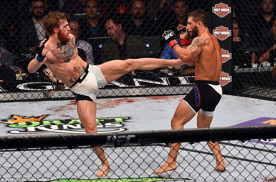McGregor aims for Mendes' midriff with a left leg kick as he starts to turn the tables in the UFC 189 contest