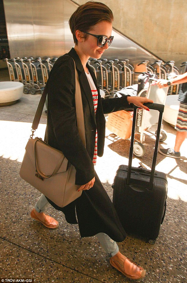 All smiles: She teamed the fitting tee with ripped jeans and a black duster jacket, polishing off the outfit with rose gold espadrilles and a stone-coloured carry-on bag, which she wore over her shoulder