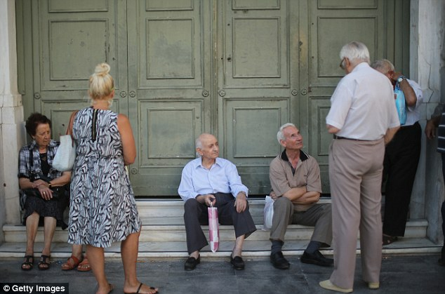 Pensioners wait to collect their money outside a National Bank of Greece branch in Athens' Kotzia Square