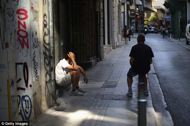 Nowhere to go: Men sit in the street in downtown Athens earlier this morning