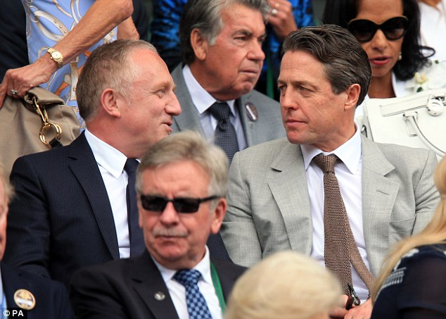 Hugh Grant, wearing a similar textured tie and suit to Benedict, chats with a fellow specator