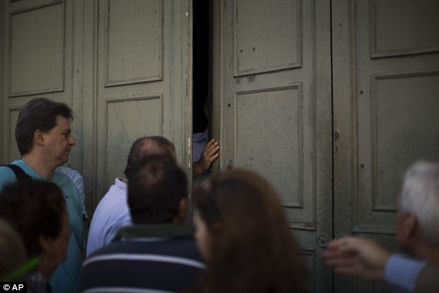 A bank employee opens the main gate of the national bank of Greece as pensioners wait to withdraw a maximum of €120 ($134) for the week in central Athens today