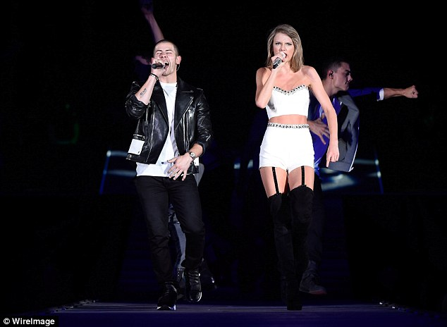 Hot stuff: The Shake It Off singer looked white hot alongside singer Nick who joined her on stage