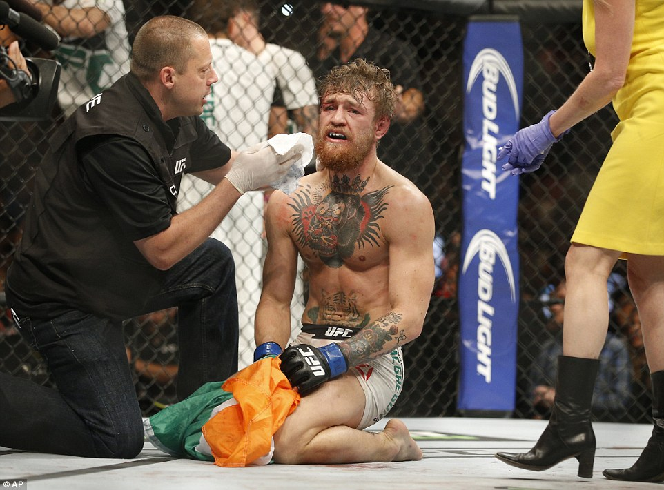 McGregor, clutching the Irish tricolor and wearing a pained expression, is cleaned up after the end of the fight