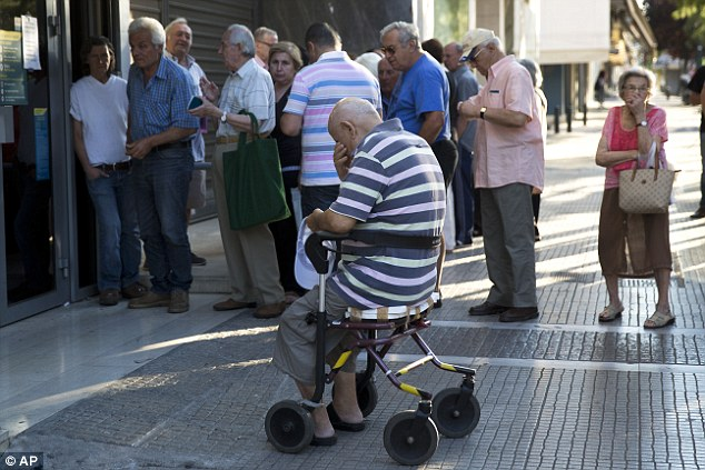 Despair: A elderly man in a wheelchair sits with his head in his hands as he waits to enter a branch of the National Bank of Greece in Athens today in the hope of withdrawing up to €120 from his pension
