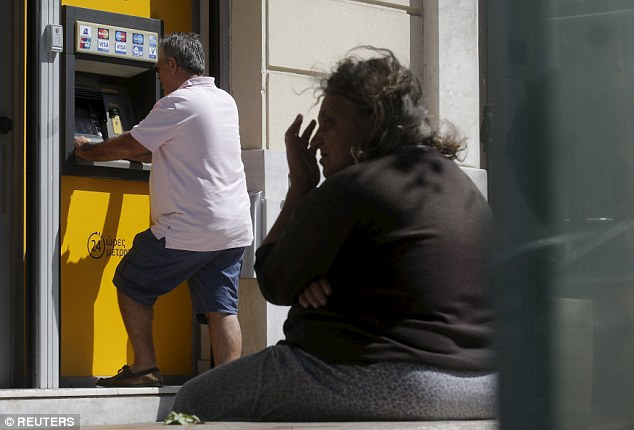 Cash economy: A man withdraws money at a Piraeus Bank branch ATM in central Athens earlier this morning