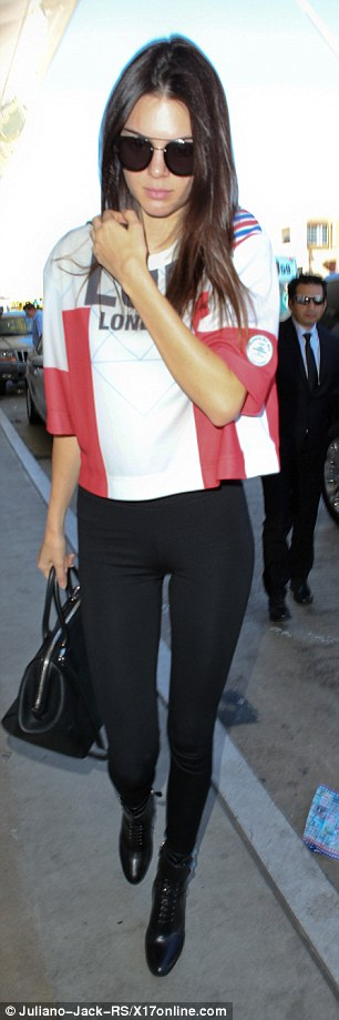 London-bound: Kendall, 19, showed off her endless legs in skin-tight black leggings, and a red and white t-shirt - thoughtfully in tune with the England flag