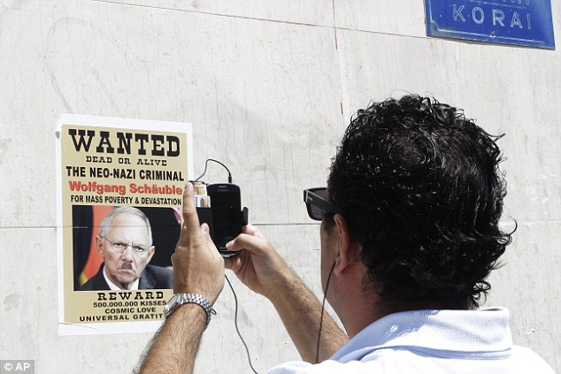 Hostility: Greeks have accused Germany of using WW2-style tactics to condemn their country to austerity. Pictured is a poster outside an Athens bank depicts German Finance Minister Wolfgang Schaeuble as a Nazi