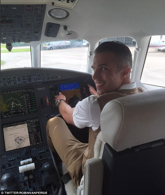 Manchester United striker Robin van Persie poses in the cockpit of the private plane he will be taking to Turkey