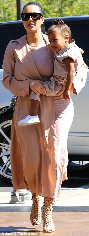 Pretty in pink: Kim wore a skintight blush coloured dress with a long, flimsy coat in a similar shade