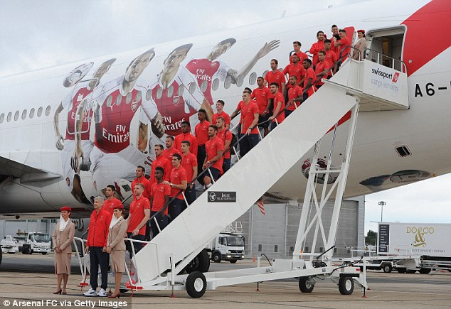 The Arsenal squad line up for a squad photo before boarding their Emirates plane to Singapore on Sunday
