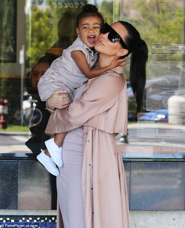 Cheek-to-cheek: Kim and North shared cuddles as they waited at the box office before the movie