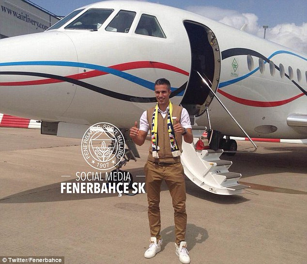 The 31-year-old, who sported a Fenerbahce scarf, was all smiles as he stands outside the plane in Manchester