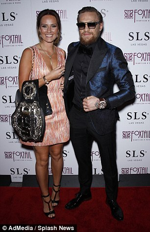 Conor McGregor and his girlfriend Dee Devlin pose a photograph as they enter the after-party