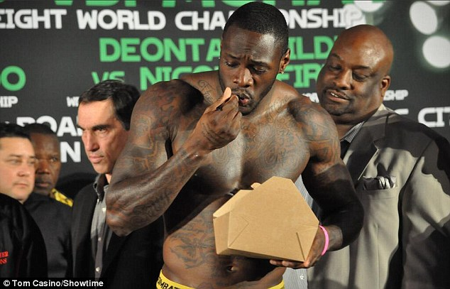 Having his cake and eating it: Deontay Wilder tucks into a strawberry shortcake on the scales