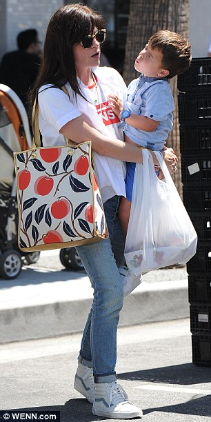 Casual cool mum: The brunette beauty sported a printed white T-shirt and cuffed skinny jeans