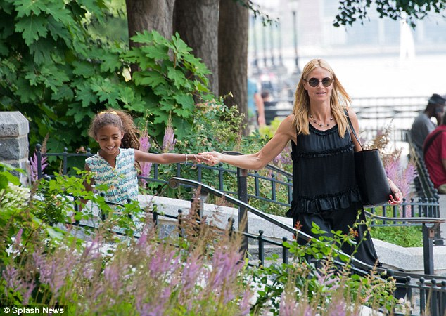 Play time: The model and TV star held her daughter Lou's hand as she walked along a wall during the Sunday afternoon outing