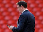 Cardiff City's Scottish manager Malky Mackay looks at his mobile phone before the start of the English Premier League football match between Liverpool and Cardiff City at Anfield stadium in Liverpool, northwest England, on December 21, 2013.  AFP PHOTO / PAUL ELLIS  RESTRICTED TO EDITORIAL USE. No use with unauthorized audio, video, data, fixture lists, club/league logos or live services. Online in-match use limited to 45 images, no video emulation. No use in betting, games or single club/league/player publications.        (Photo credit should read PAUL ELLIS/AFP/Getty Images)