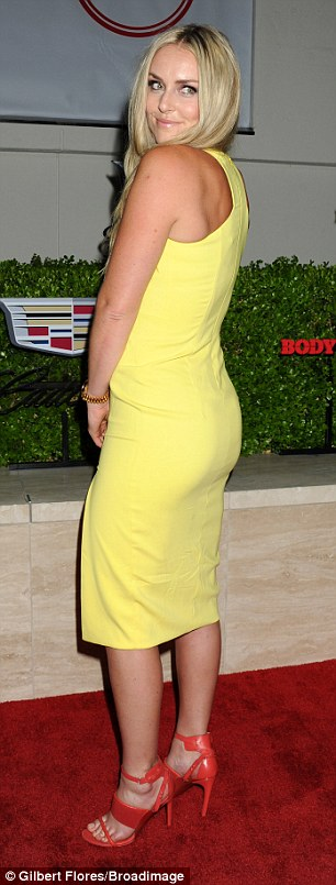Bright star: Skiing champion Lindsey  turned heads in sexy yellow dress, which showed off her curves