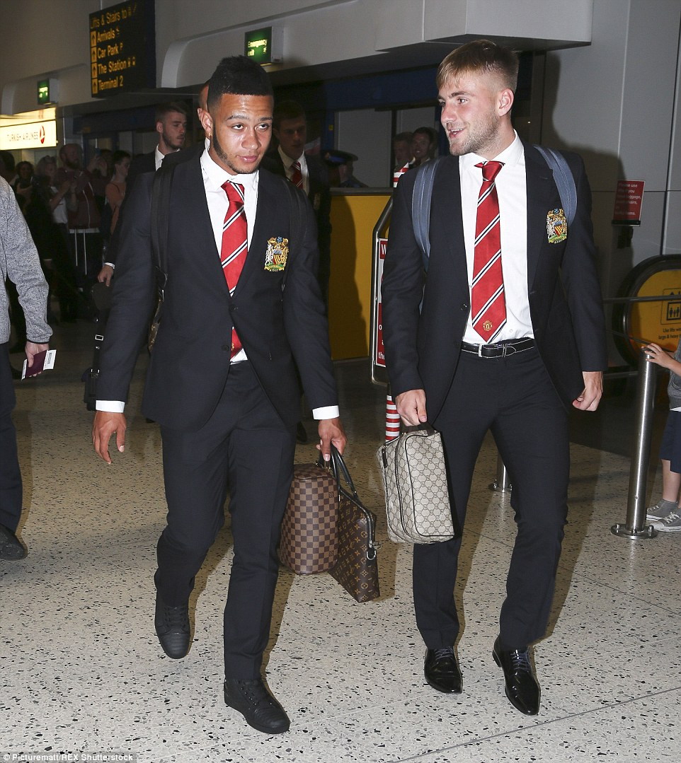 Fellow new signing Depay (left) and Luke Shaw (right) make their way to the luggage check-in ahead of their flight to Seattle
