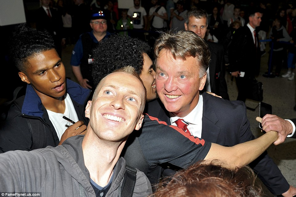 A number of fans crowd around Van Gaal, with one fan taking a selfie while another gives him a big hug, with the Dutchman all smiles