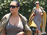 Thursday, July 16, 2015 - Kim Kardashian squeezes her growing baby bump into a tight, ribbed dress and covers up with a long trench during an outing to Fred Segal in West Hollywood.  The pregnant reality star had a secret fan learing at her from a storage unit in the parking lot.  Creepy! \nAdriano/X17online.com