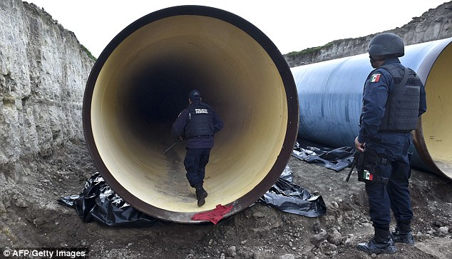 Officers search huge construction pipes on the large building site next to the prison on Sunday. He is known for his network of elaborate tunnels which he uses to transport drugs over the U.S border
