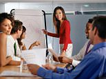 A posed picture of a young professional woman giving a presentation to her work colleagues. A3FX9E.jpg