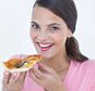 Beautiful woman eating a pizza on white background