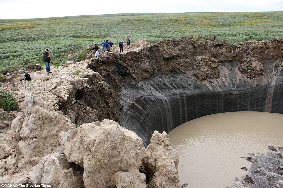 Researchers have been studying the craters, which show no signs of charring or burning around the edge, and are already forming into lakes. The image above shows scientists and journalists on the edge of the crater B1 in the Yamal region of Russia