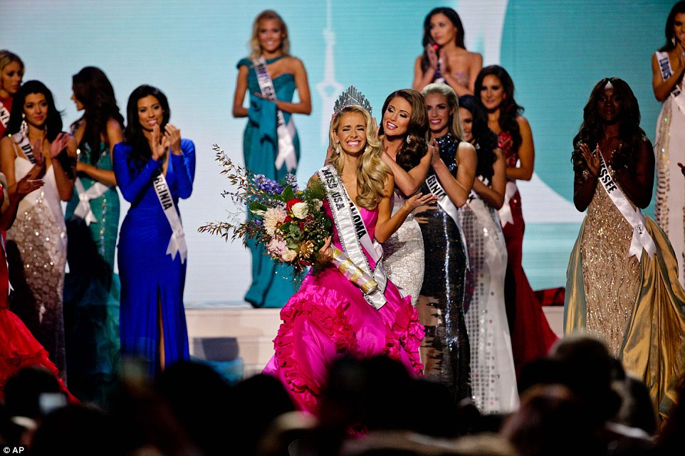 Miss Oklahoma Olivia Jordan lifts her arm in shock as she's crowned Miss USA by Miss USA 2014 Nia Sanchez