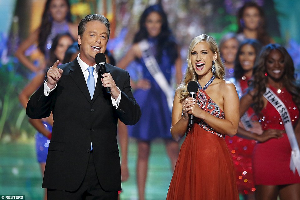 Hosts Todd Newton and former Miss Wisconsin Alex Wehrley speak on stage as Miss USA contestants pose behind them during the competition