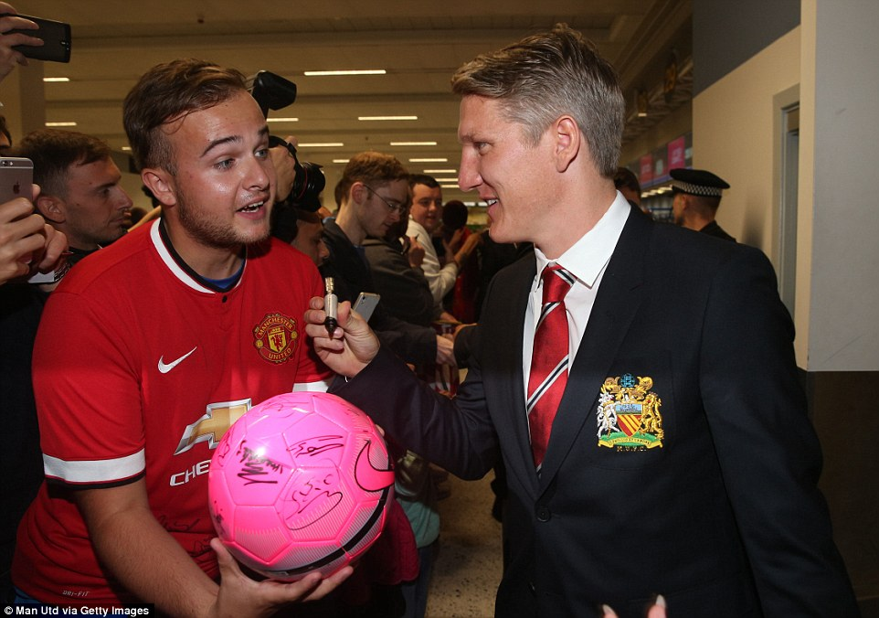 The 30-year-old Germany international signs a football for a Manchester United fan at the airport on the way to Seattle on Monday