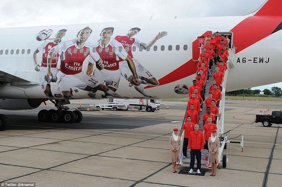 Arsenal boss Arsene Wenger stands at the front as the team pose for a picture before leaving Stansted Airport