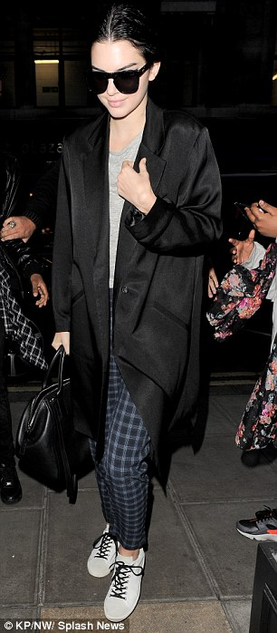Casual chic: The 19-year-old model dressed down in tartan Native Youth 'Spearhill' trousers and lace-up flats after her busy day