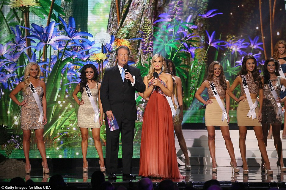 Hosts Todd Newton and Former Miss Wisconsin Alex Wehrley speak on stage as Miss USA contestants pose in nude dresses and heels during the competition
