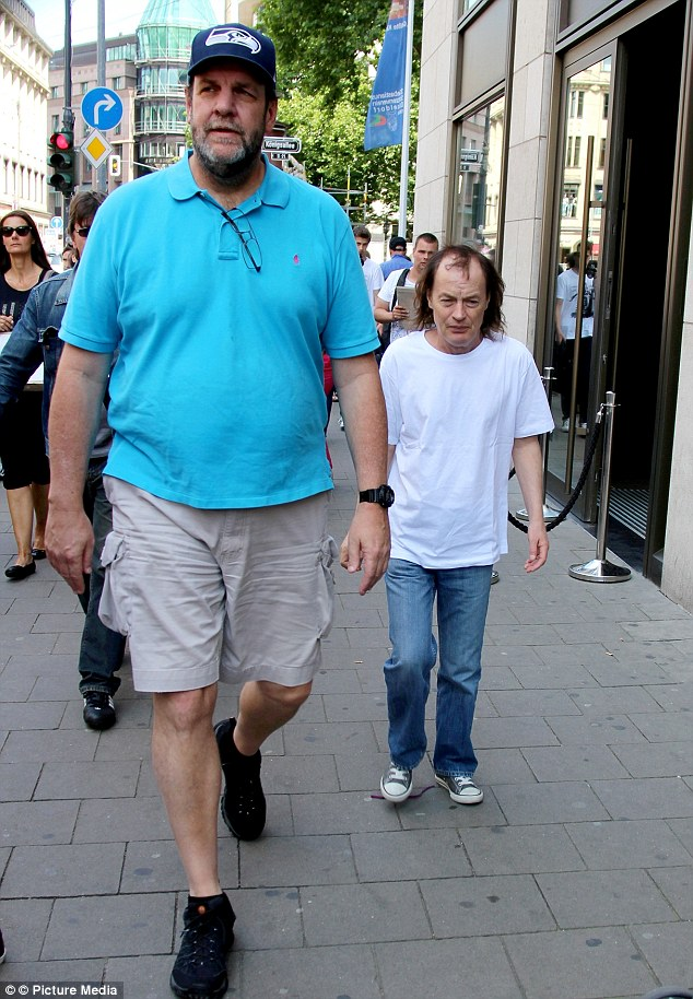 The long and short of it: AC/DC legend Angus Young looked every inch his diminutive frame beside his lofty bouncer as they strolled around Duesseldorf, Germany, on Saturday