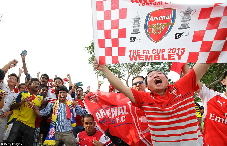Supporters cheer wildly as they wait for the Arsenal stars to emerge from the Changi Airport