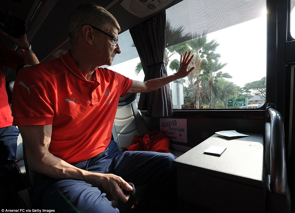 Arsenal boss Arsene Wenger puts his hand out to supporters after leaving the airport on the team coach