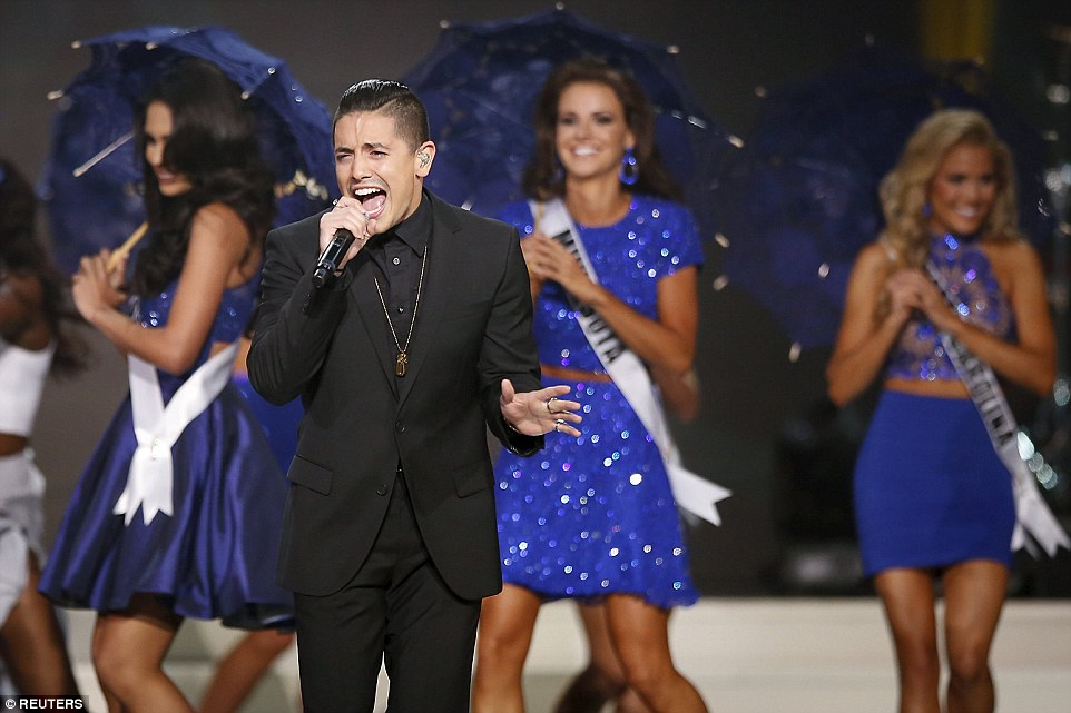 Singer Stefano Langone performs on stage on Sunday as the 2015 Miss USA contestants dance with umbrellas behind the performer