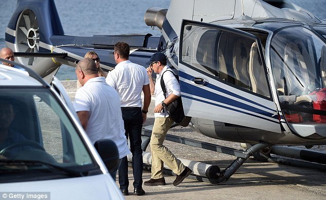 Discreet: The pair nipped onto the helipad as they were surrounded by security