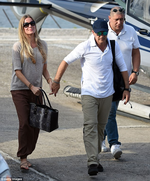 Taking her hand: Antonio can't resist reaching out for his glamorous partner as they head to the terminal