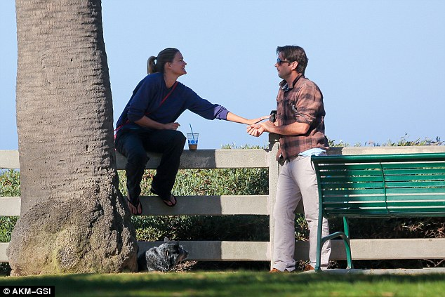 Still close: Sitting on a wooden fence, Meg pawed at the handsome star as they talked things through