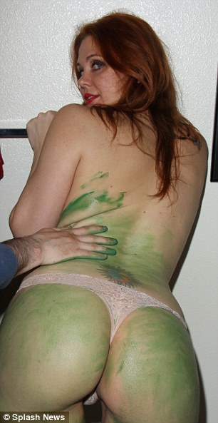 She left little to the imagination as she applied the jade shade to her skin